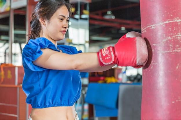 Porträt von tragenden boxhandschuhen der jungen asiatischen frau, die boxen in der turnhalle üben.