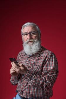 Porträt von tragenden brillen eines älteren mannes, die in der hand intelligentes telefon gegen roten hintergrund halten