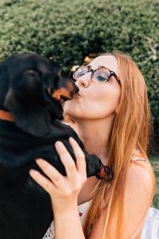 Porträt von tragenden schauspielen einer jungen frau, die ihren hund küssen