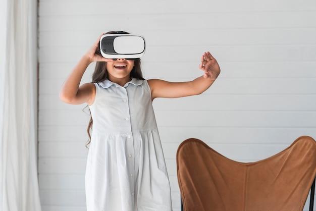 Porträt von tragenden schutzbrillen der virtuellen realität des mädchens, die ihre hand in einer luft berühren