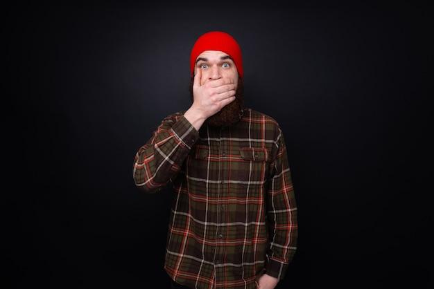 Porträt von überraschten bärtigen männern, die seinen mund von hand bedecken, während sie isoliert auf dunkler wand stehen