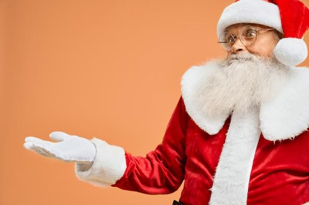 Porträt von überraschter santa claus mit offener palme im studio