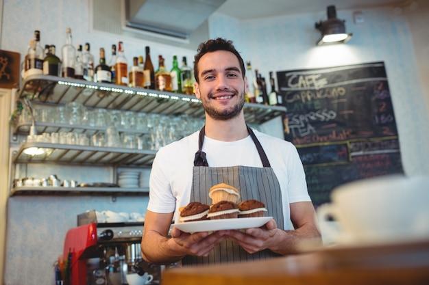 Porträt von überzeugtem barista mit kleinen kuchen an der kaffeestube