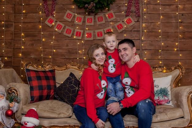 Porträt von vater, mutter und sohn, die auf einer couch zu hause nahe dem weihnachtsbaum sitzen