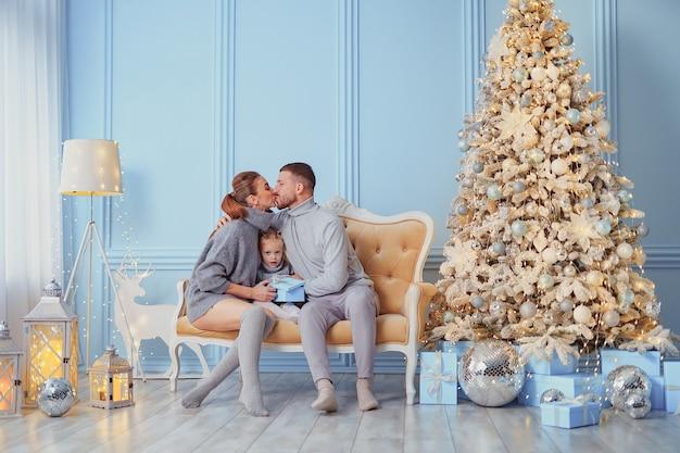 Porträt von vater, mutter und tochter, die zu hause auf einer couch in der nähe des weihnachtsbaums sitzen, sind alle
