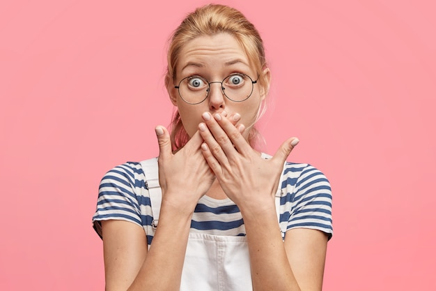 Porträt von verblüfften blonden weiblichen blicken mit betäubtem ausdruck