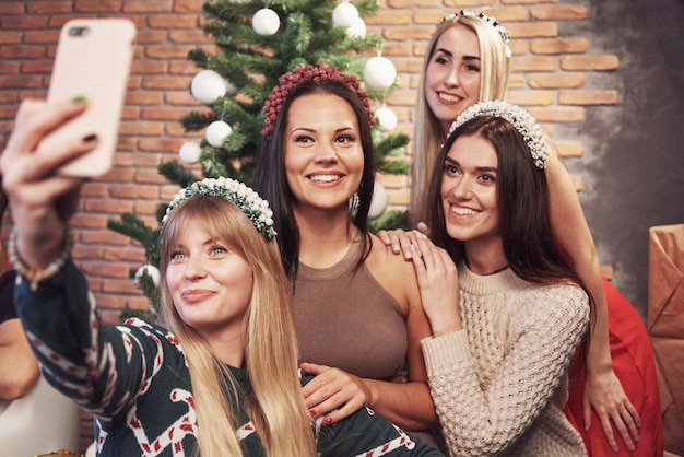 Porträt von vier lächelnden mädchen mit krone auf dem kopf machen selfie-foto. neujahrsgefühl. fröhliche weihnachten