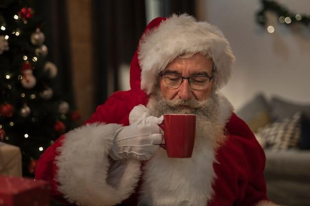 Porträt von weihnachtsmann ein weihnachtsgetränk trinkend
