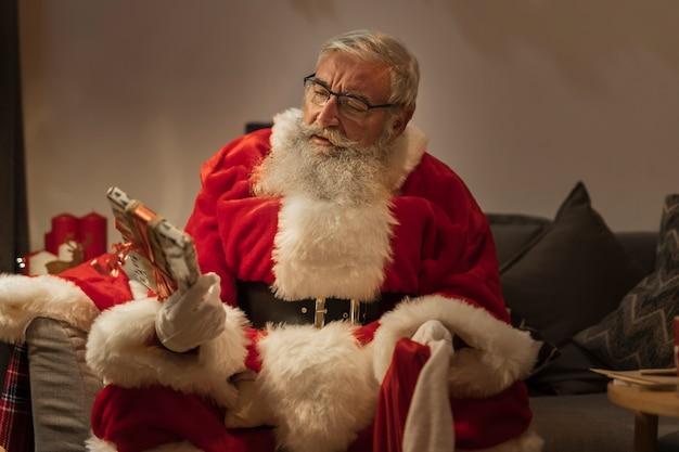 Porträt von weihnachtsmann geschenke überprüfend