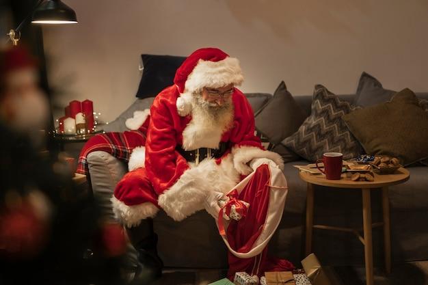Porträt von weihnachtsmann geschenke vorbereitend