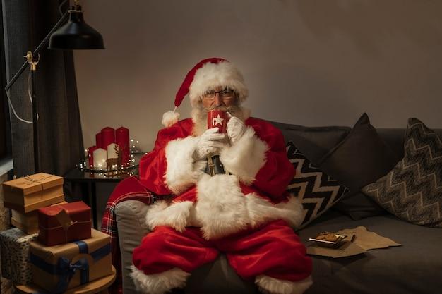 Porträt von weihnachtsmann sitzend auf der couch