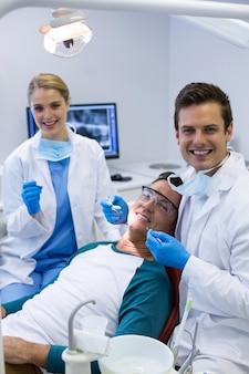 Porträt von zahnärzten, die einen männlichen patienten mit werkzeugen untersuchen