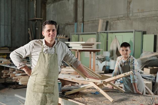 Porträt von zufriedenen möbelherstellern in schürzen, die am schreibtisch mit holzstuhl und spänen in werkstatt, familienunternehmen stehen