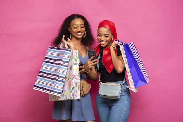 Porträt von zwei afrikanischen frauen, die einkaufstaschen halten, während sie etwas in ihrem smartphone reagieren