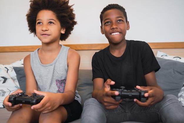 Porträt von zwei afroamerikanischen brüdern, die zu hause videospiele spielen. lifestyle- und technologiekonzept.