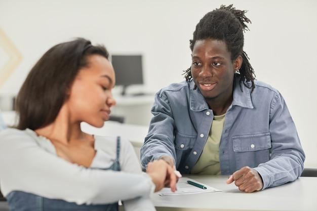 Porträt von zwei afroamerikanischen schülern, die während des unterrichts in der schule notizen übergeben, platz kopieren