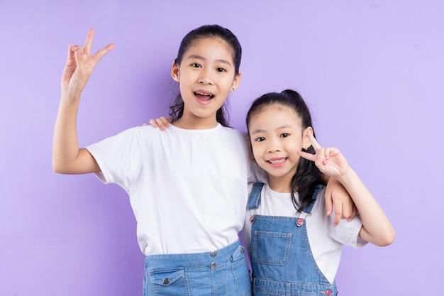 Porträt von zwei asiatischen mädchen auf lila hintergrund