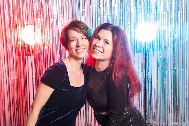 Porträt von zwei attraktiven glücklichen frauen in den abendkleidern, die kamera über silbern gefärbten glänzenden hintergrund umarmen und betrachten. geburtstagsfeier, feiertage und nachtclubkonzept.