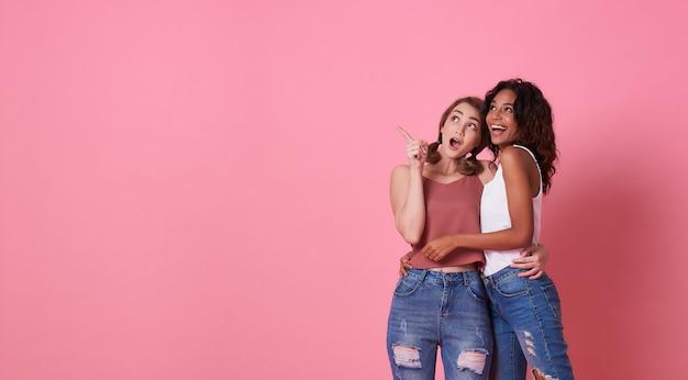 Porträt von zwei aufgeregten jungen frauen, die mit ihrem finger zeigen auf kopienraum lokalisiert über rosa fahnenhintergrund mit kopienraum stehen.