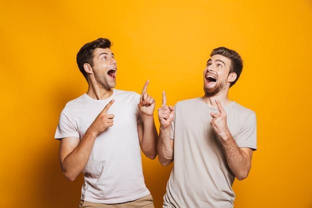 Porträt von zwei aufgeregten jungen männern, die beste freunde zeigen