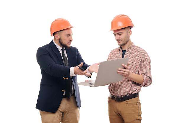 Porträt von zwei bauherren in den schützenden orange helmen, die auf weißem lokalisiertem hintergrund stehen und laptopanzeige betrachten. bauprojekt besprechen