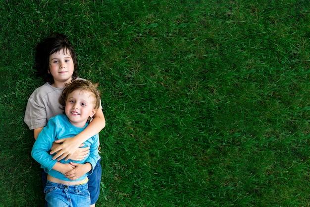Porträt von zwei brüdern, die auf einem gras in einem park liegen und sich umarmen. lächelnde glückliche kinder im freien. geschwisterfreundschaft.
