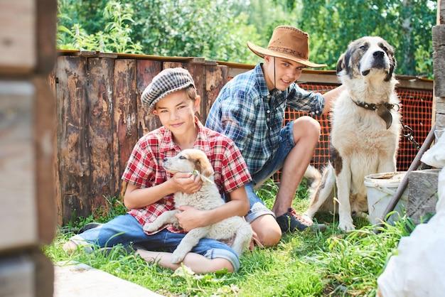 Porträt von zwei brüdern, die im platz mit hunden auf dem gras im dorf sitzen