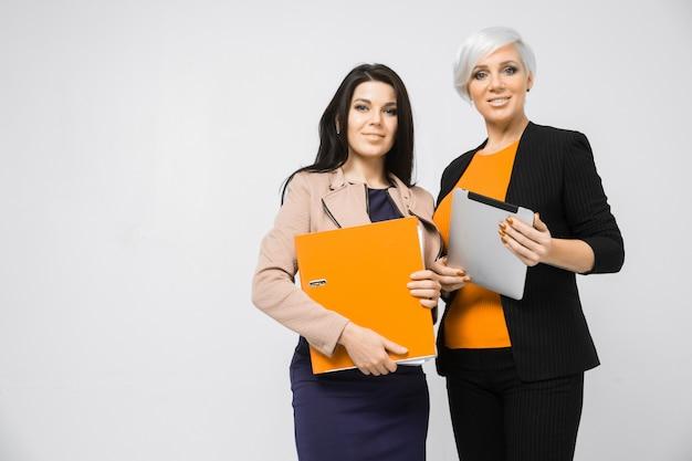 Porträt von zwei damen mit dokumentenordner und tablette in der hand lokalisiert auf weißem hintergrund