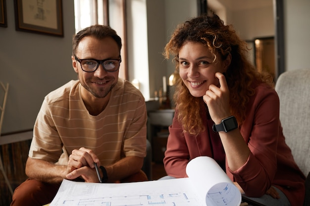 Porträt von zwei erfolgreichen designern, die in die kamera lächeln, während sie mit blaupause zusammen im büro arbeiten