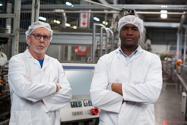 Porträt von zwei fabrikingenieuren, die mit verschränkten armen stehen