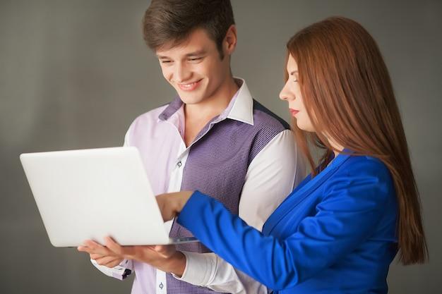 Porträt von zwei fachleuten, die einen laptopschirm betrachten
