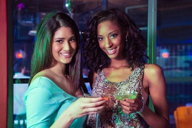 Porträt von zwei frauen, die cocktail in der bar haben