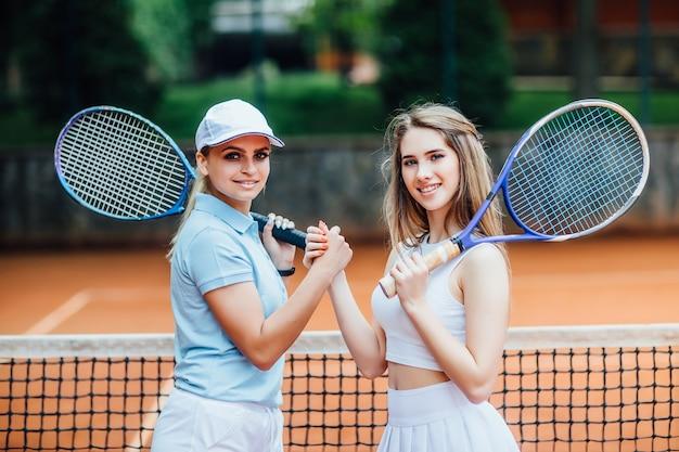 Porträt von zwei frauen, die draußen im tennis zusammen spielen.