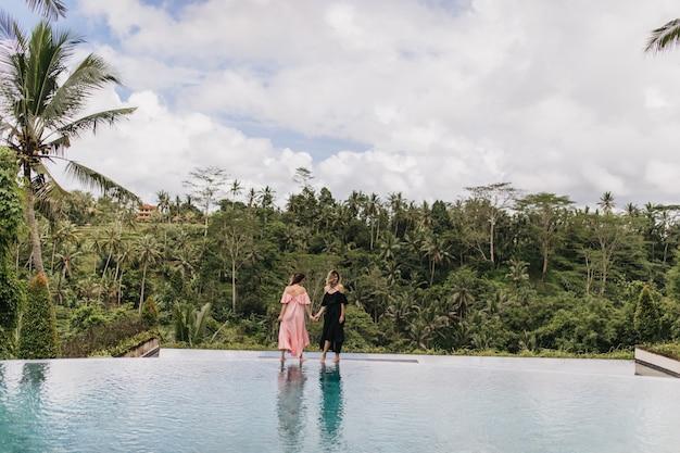 Porträt von zwei frauen, die nahe außenpool am exotischen resort aufwerfen. foto von anmutigen damen in kleidern, die auf natur stehen.