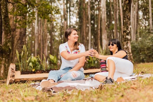 Porträt von zwei frauen, die partnerinfusion im park trinken
