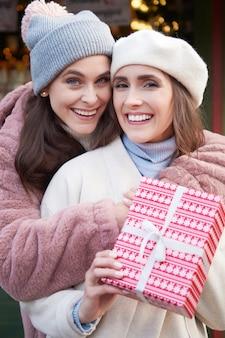Porträt von zwei frauen mit weihnachtsgeschenk