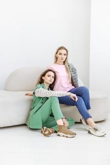 Porträt von zwei frauenmodellen, die in moderner kleidung auf einem sofa sitzen und die kamera betrachten