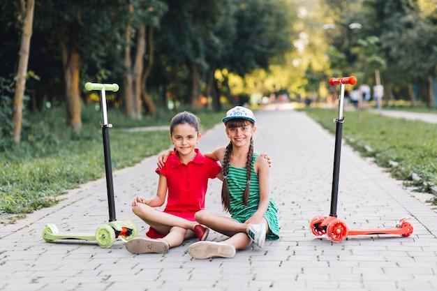 Porträt von zwei freundinnen, die auf gehweg mit ihren trittrollern im park sitzen