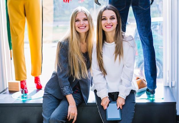 Porträt von zwei freundinnen, die im kleidungsspeicher mit digitaler tablette sitzen