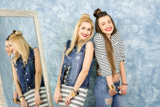 Porträt von zwei freundinnen lässig gekleidet in der nähe des spiegels auf dem blauen wandhintergrund