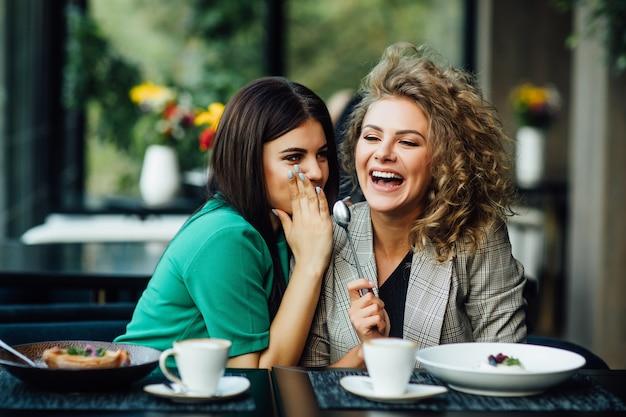 Porträt von zwei freundinnen verbringen zeit zusammen, trinken kaffee im café, haben spaß beim essen von dessert, kuchen. gesagtes geheimnis für andere. glück.
