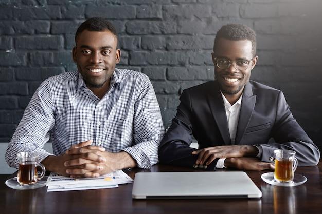 Porträt von zwei fröhlichen afroamerikanischen geschäftsleuten oder geschäftspartnern, die am schreibtisch sitzen