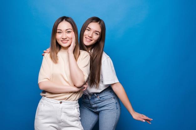 Porträt von zwei fröhlichen jungen frauen, die zusammen stehen und finger lokalisiert über blaue wand zeigen