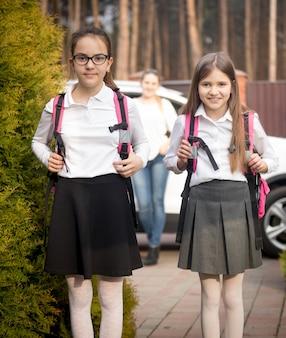 Porträt von zwei fröhlichen mädchen, die morgens zur schule gehen