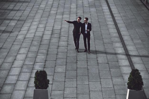 Porträt von zwei geschäftsleuten, die beim gehen im freien über das neue projekt diskutieren.