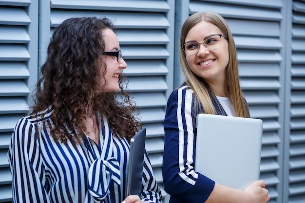 Porträt von zwei geschäftsmännern, die mit laptops in den händen stehen, neues projekt. junge geschäftskollegen diskutieren über büroarbeit. erfolgreicher weiblicher manager mit brille. unternehmenskonzept