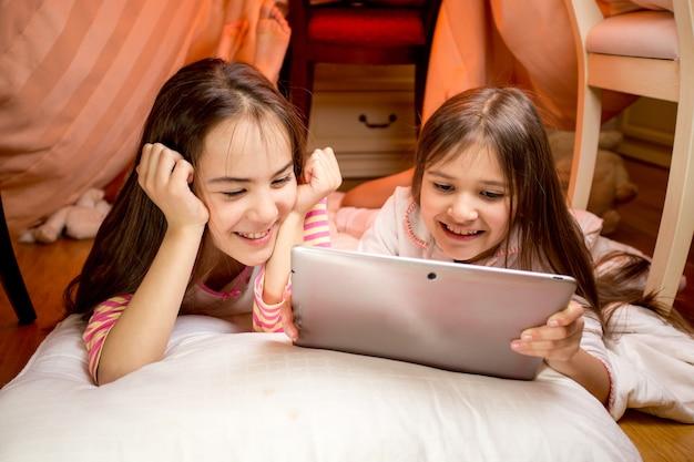 Porträt von zwei glücklich lächelnden mädchen, die auf dem boden liegen und ein digitales tablet verwenden