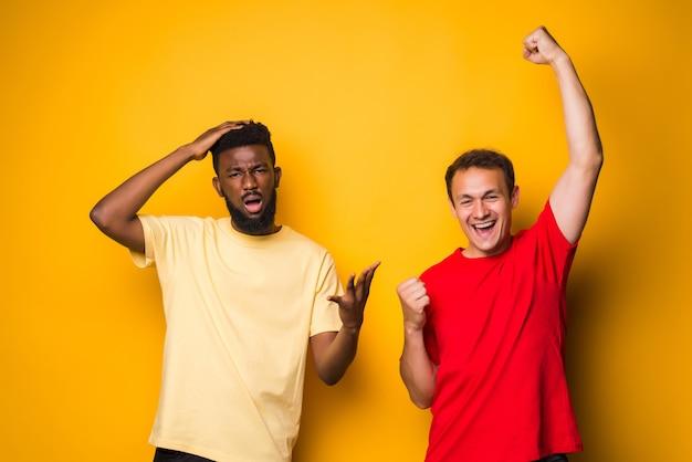 Porträt von zwei glücklichen jungen männern, die emotionen gewinnen und verlieren, nachdem fußball über gelber wand isoliert ist?