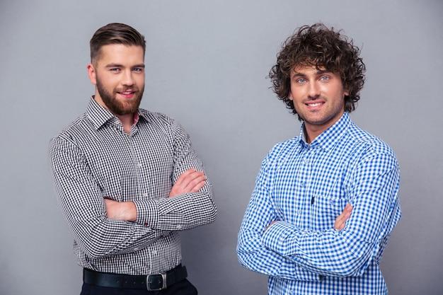 Porträt von zwei glücklichen männern, die mit verschränkten armen auf grauer wand stehen