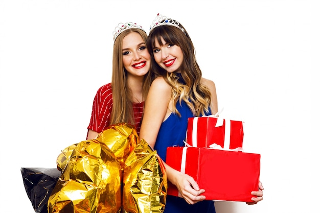 Porträt von zwei hübschen frauen mit hellen partyballons und geschenkboxen